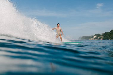 side view of young man in wet t-shirt riding waves on surfboard while having vacation