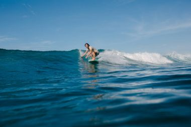 athletic man in wet t-shirt riding waves on surfboard on sunny day