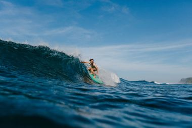 professional surfer in wet t-shirt riding waves on surfboard on sunny day