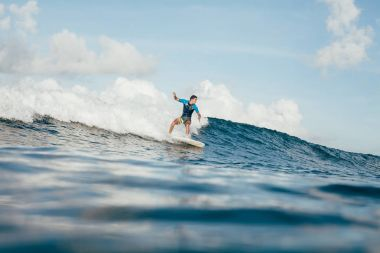 side view of young sportsman in wetsuit having fun on surfboard on sunny day