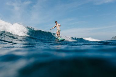 handsome man in wet t-shirt riding waves on surfboard on sunny day