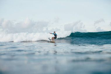 young sportsman in wetsuit riding waves on surfboard on sunny day