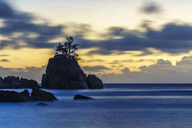 Mystic sunset over rock with single tree. seychelles 1