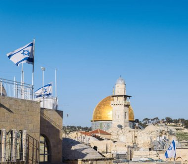 View on Dome of the Rock mosque in Jerusalem and Israeli flags from a balcony during a sunny day with copy space