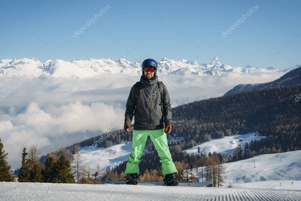 Full length shot of a smiling snowboarder standing on the slope in the mountains, looking to the camera at winter ski resort Pila, Aosta, Italy