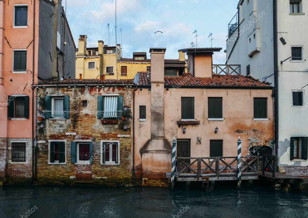 Facade of partially mossy old brick house with wooden vintage door on narrow canal in Venice, Italy