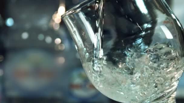 Vystřižení, samostatný closeup vylévá jasné minerální vodu do průhledné sklenice na víno