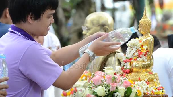 people showering buddha statue in Songkran festival