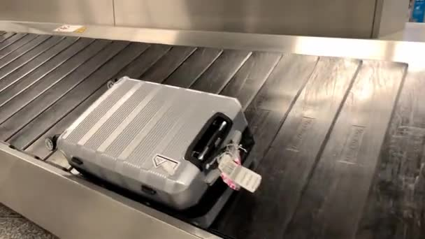 suitcases roll on a conveyor belt in the baggage claim room at the airport, travel concept