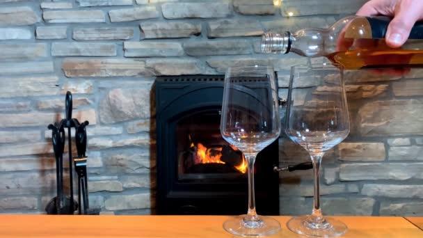 Orangefarbene Flamme brennt im Kamin, ein Mann gießt Wein aus einer Flasche in zwei Gläser, ein Konzept für einen romantischen Abend