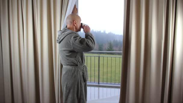 muž středního věku v šedém županu pije čaj nebo kávu z hrnku u okna