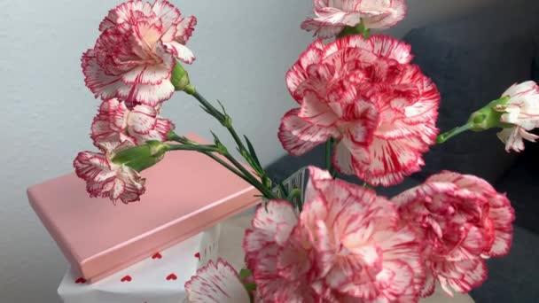 kytice růžových květin karafiátů stojí ve váze, koncept sladkého domova