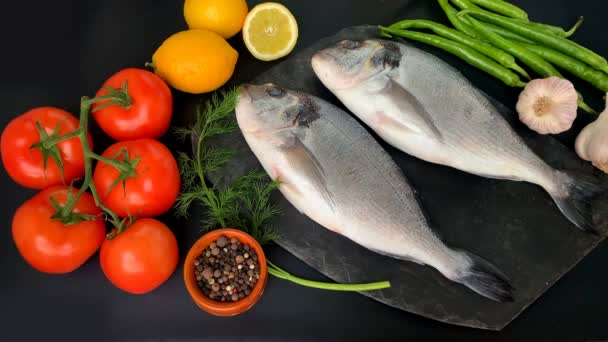 lemons, tomatoes, hot peppers, two carcasses of fresh raw Atlantic sea fish Sparus aurata and a sprig of dill lie on a black background, cooking concept