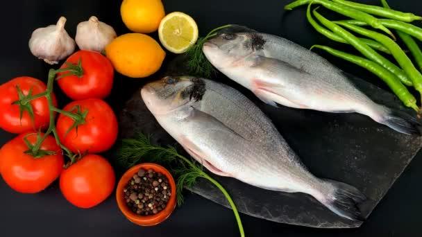 citrom, paradicsom, csípős paprika, két hasított friss nyers atlanti tengeri hal Sparus aurata és egy csipet kapor fekszenek a fekete háttér, főzés koncepció
