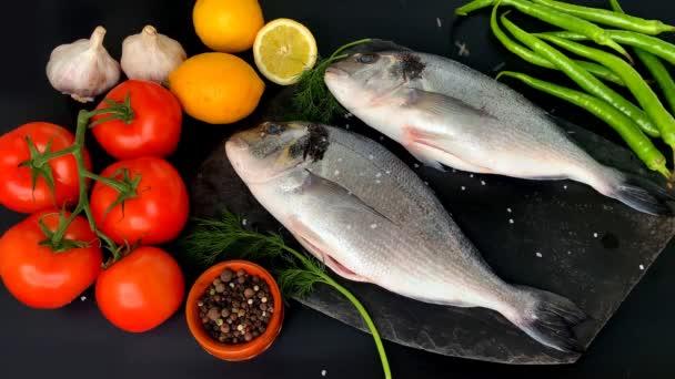Zitronen, Tomaten, Paprika, zwei Kadaver frischer Atlantikrohfisch Sparus aurata und ein Zweig Dill liegen auf schwarzem Hintergrund, Kochkonzept