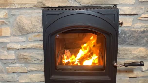 muž a žena zahřívá ruce u jasně oranžového ohně v černém krbu, útulný domácí koncept