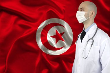 male doctor with a stethoscope on the background of the silk national flag of Tunisia, concept of national medical care, health, insurance, tourism