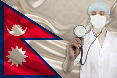 male doctor with a stethoscope on the background of the Nepal silk national flag, concept of national medical care, health, insurance, tourism
