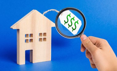 A magnifying glass looks at a wooden house figure and price tag. Selling a house or auction. Realtor Services. Buying liquid and expensive real estate and investments. housing, credit and
