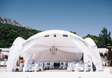 beautifully decorated wedding tent and wedding banquet on a background of mountains and sky