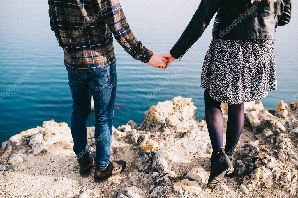 young loving couple walking and holding hands on a rock with a beautiful view of the sea and mountains