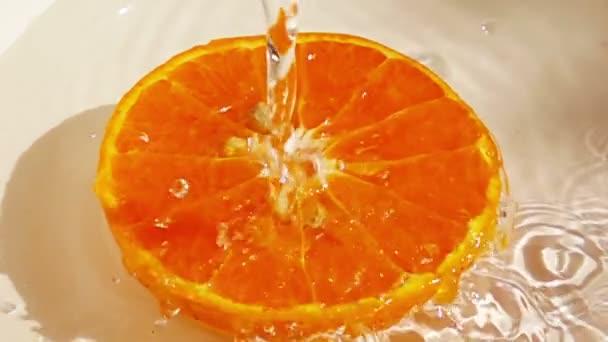 voda stříkající na pomerančové ovoce zpomaleným pohybem.