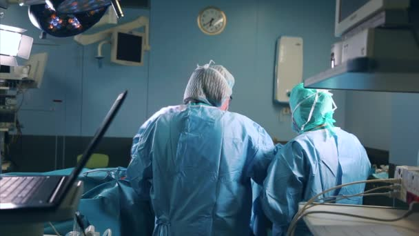 Professioneller Chirurg steht mit verschränkten Armen in der chirurgischen Maske. Im Hintergrund moderner Krankenhaus-Operationssaal mit laufenden Operationen.