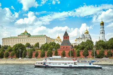 A modern river ship in the center of Moscow sails past the Kremlin. Picturesque modern urban architecture. Tourism, rest in the city, river transport.