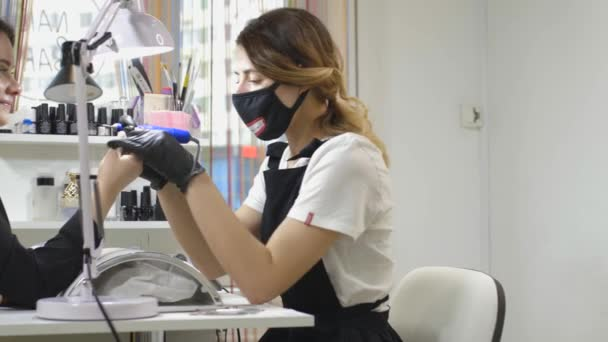 Nehet péče. Mistr a spokojený klient během ošetření nehtů. Koncepce kosmetického salonu péče o nehty, manikúra. Kosmetický průmysl zákaznický servis. 4K