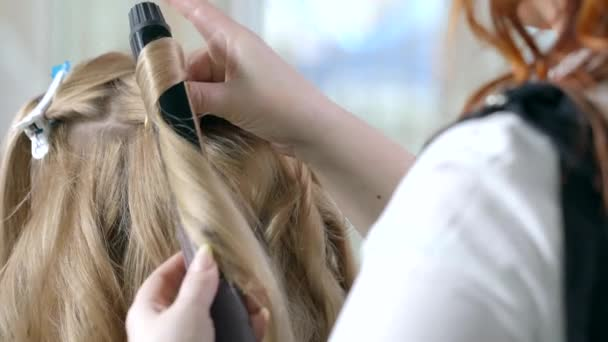 Close up of the hands of a professional hairdresser doing a curly hairstyle using a curling iron. The artist creates a curl hairstyle for long blonde hair in a beauty studio.