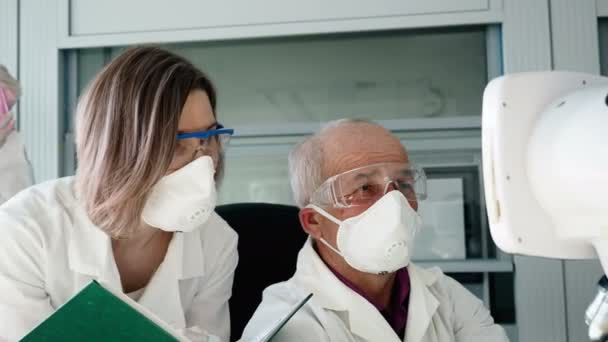 Doctor with colleague do expertise by microscope