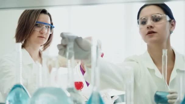 Dvě ženy pracují v laboratoři s zkumavky