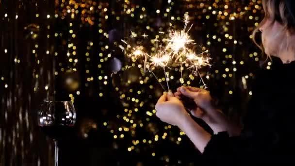 Žena se usměje a drží v rukou jiskru roku2020. Šťastný nový rok 2020.