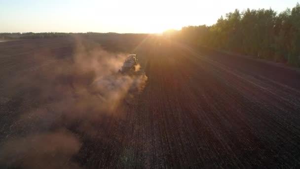 Zemědělská půda podle zemědělské techniky nebo traktoru při západu slunce, přírodní statek