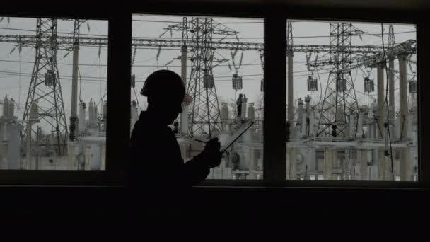 Silueta inženýra v poznámkách k oknům plán na těžký průmysl, pracovní lidé