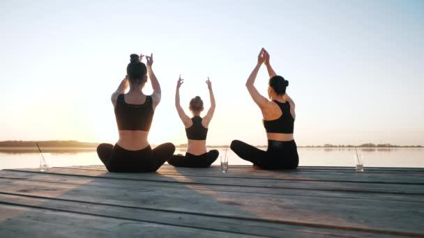 Gruppenmädchen macht Yoga-Übungen, Meditation sitzt in Lotusposition zusammen