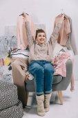 Fotografia ragazza sorridente che si siede sulla poltrona e ganci con vestiti in possesso nelle mani