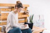 Fotografie usmívající se dívka sedí na stole v kanceláři a napsat něco do poznámkového bloku