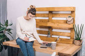 lány ül a Hivatal asztal és írásban valami notebook