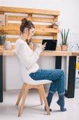 oldalnézetből a lány ül a szék hivatal és használ smartphone