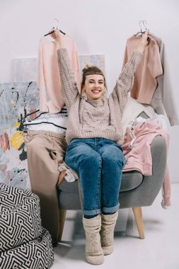 smiling girl sitting on armchair and holding hangers with clothes in hands