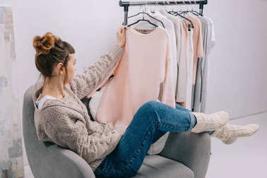 side view of girl sitting on armchair and looking at shirt in hand