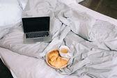 šálek kávy a croissanty na desce a otevřené laptop na posteli