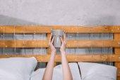 körülvágott kép-csésze kávéval a kezében tartja, és az ágyban fekve lány