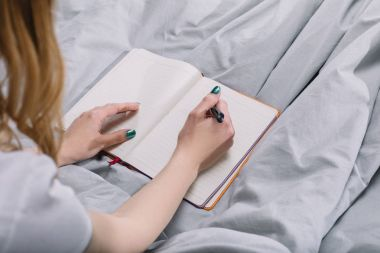 cropped image of girl writing something to notebook