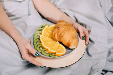 cropped image of girl holding plate with fruits and croissant
