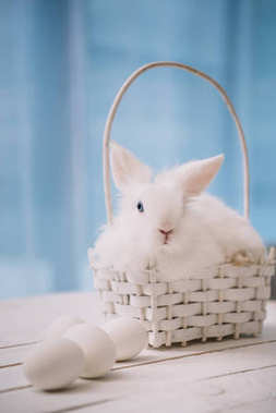 white easter rabbit sitting in basket with eggs on table
