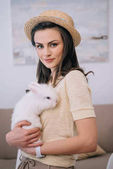 Fotografie young stylish woman in hat holding cute white rabbit