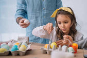 beautiful child painting easter eggs with father
