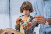 focused little kid painting easter eggs with father